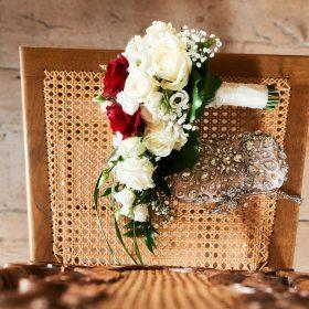 Creme und rotgrüner Brautstrauß aus Rosen von oben auf dem braunen Holzstuhl liegend - Trauzimmer Schloss Schöningen © Hochzeitsfotograf www.hochzeitsverliebt.de